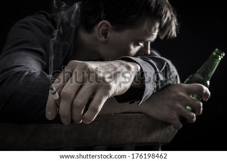 Portrait of a smoking, beer drinking, depressed man - stock photo