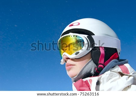 Portrait of a snowboarder at Krasnaya Polyana in the helmet and protective mask on background of blue sky - stock photo