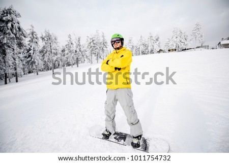 Portrait of a snowboarder in colorful winter sports clothes outdoors at the snowy mountains