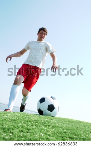 Portrait of a soccer player going to kick ball on football field - stock photo