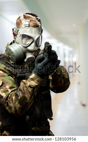 Portrait Of A Soldier With Gas Mask Aiming With Gun in a passage way - stock photo