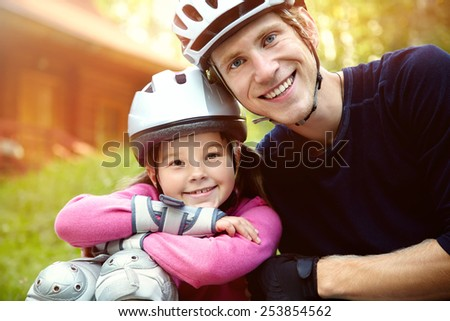 portrait of a sports dad and daughter in a helmet. Dad with his little daughter on the skates - stock photo