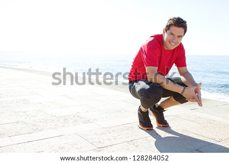 Portrait of a sports man crouching down on a track by the sea on a sunny day, smiling against a blue sky. - stock photo