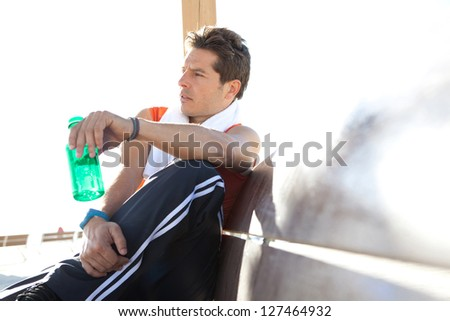 Portrait of a sports man relaxing sitting down on a wooden bench and holding a bottle of water, against a sunny sky.