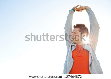 Portrait of a sports man stretching his arms up in the air against a sunny blue sky with sun rays filtering through his neck. - stock photo