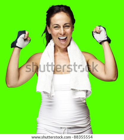 portrait of a sporty middle aged woman gesturing good symbol against a removable chroma key background - stock photo