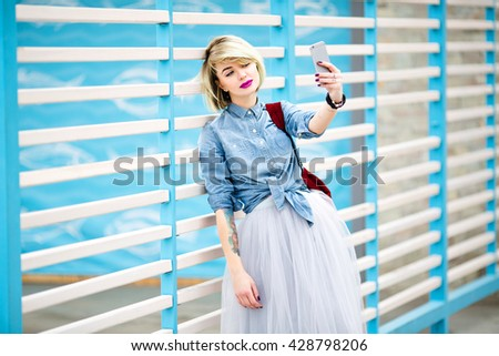 Portrait of a standing girl with blond hair,pink lips and nude make up making a selfie on a smartphone leaning on blue and white stripes fence on the background and wearing blue denim shirt,grey skirt - stock photo