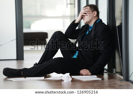 Portrait of a stressed disappointed businessman sitting alone on floor in office - stock photo