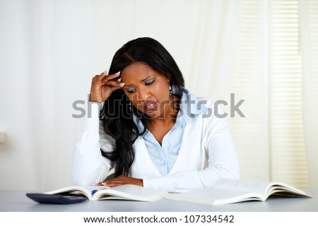 Portrait of a stressed young black woman reading a book at home indoor - stock photo