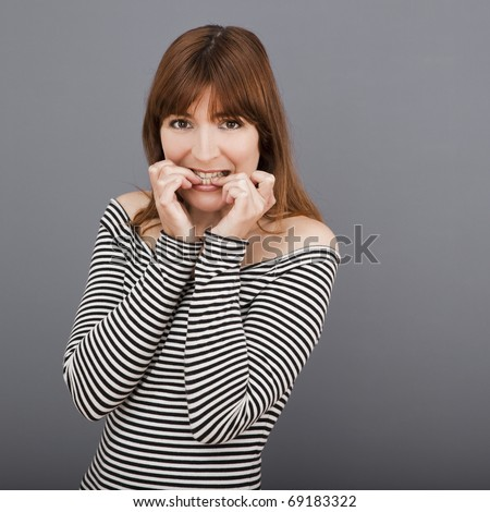 Portrait of a stressed young woman biting nails - stock photo