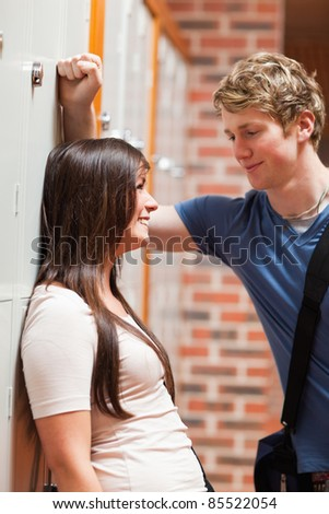 Portrait of a student couple flirting in a corridor - stock photo