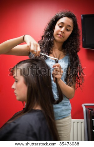 Portrait of a student hairdresser cutting hair with scissors - stock photo