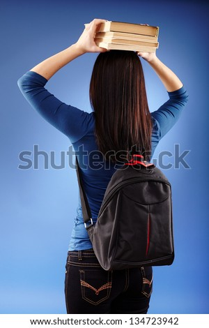 Portrait of a student holding books on her head on blue background