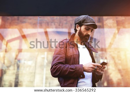 Portrait of a stylish adult men chatting on mobile phone while standing on the street in cool autumn day, fashion male with trendy look using his mobile phone during strolling in urban setting  - stock photo