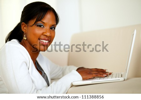 Portrait of a stylish girl looking at you while working on laptop at home indoor. With copyspace