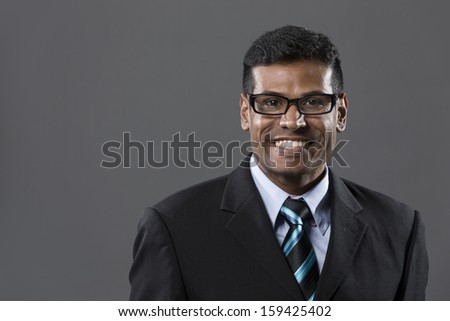 Portrait of a stylish Indian businessman standing in front of a dark grey background. - stock photo