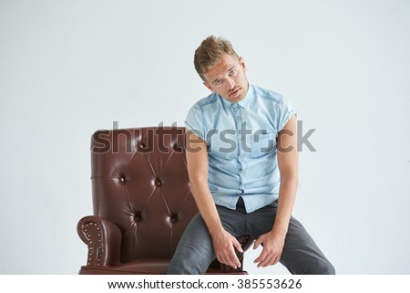 Portrait of a stylish intelligent man, small unshaven, charismatic, blue shirt, sitting on a brown leather chair, dialog, negotiation, short sleeve, brutal, hairstyle, emotions, indifference, fatigue