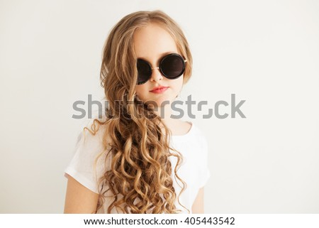 Portrait of a stylish little girl in sunglasses - stock photo