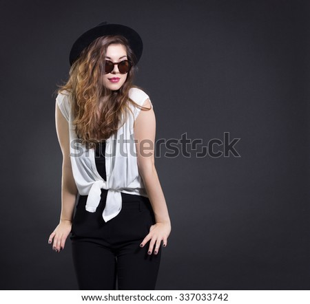Portrait of a stylish woman in a black hat and sunglasses on a dark background.