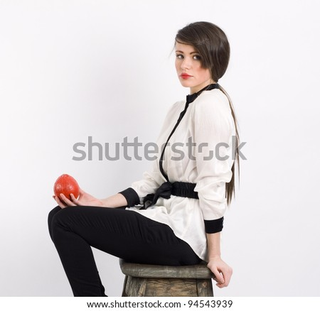 Portrait of a stylish  woman on a white background with red fruit in his hand. - stock photo