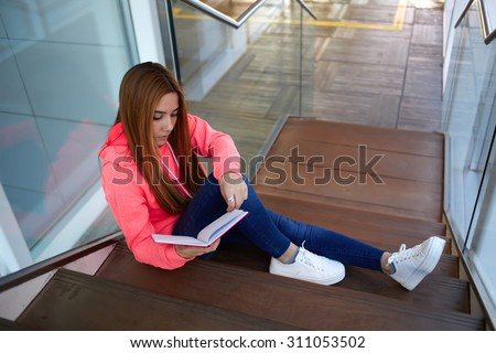 Portrait of a stylish young college student read her notebook while sitting on the stairs of campus interior, teenager girl with long hair preparing for classes or exams at school, learning hard - stock photo