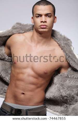 Portrait of a stylish young fashion male model on gray background. - stock photo