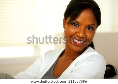 Portrait of a stylish young woman looking at you at home indoor. With copyspace