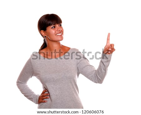 Portrait of a stylish young woman pointing and looking up on grey dress standing over white background - copyspace - stock photo