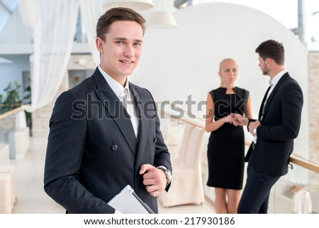 Portrait of a successful and confident businessman. Young man in formal wear holding a the tablet and smiling at the camera while his colleague talking on the background