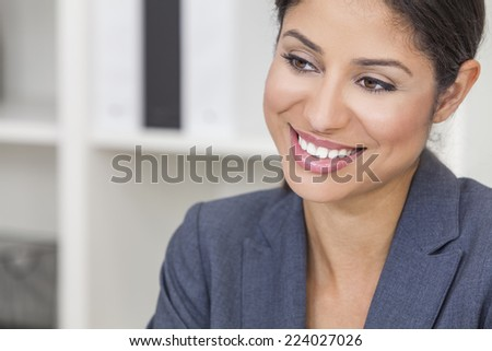 Portrait of a successful beautiful young Latina Hispanic woman or businesswoman in her office smiling with perfect teeth - stock photo