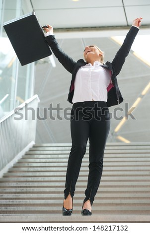 Portrait of a successful business woman celebrating with arms raised - stock photo