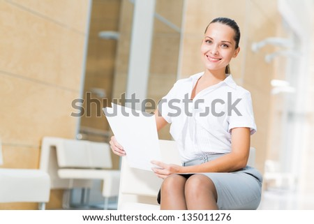 Portrait of a successful business woman in the office, holding papers and smile - stock photo