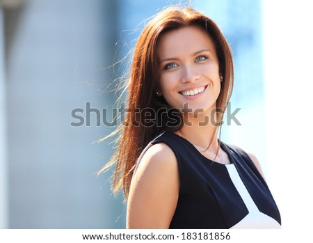 Portrait of a successful business woman smiling. Beautiful young female executive in an urban setting  - stock photo