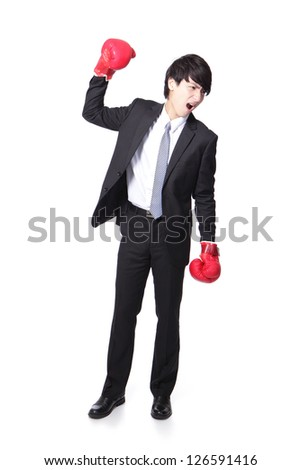 Portrait of a successful businessman arise arm with boxing gloves in full length isolated over white background, asian model - stock photo
