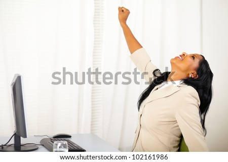Portrait of a successful executive female at work while celebrating victory - stock photo