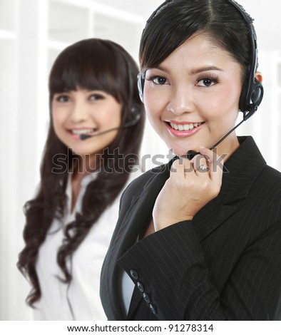 Portrait of a successful female call centre employee wearing a headset. in white background - stock photo