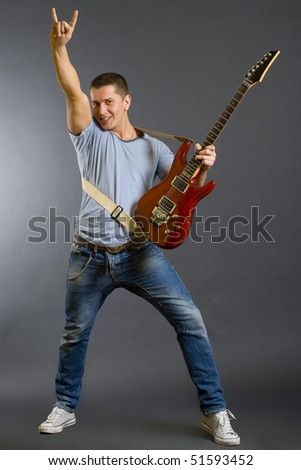 Portrait of a successful rock star holding an electric guitar and making a rock sign on a dark background - stock photo