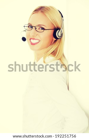 Portrait of a successful young female call centre employee wearing a headset against white background - stock photo