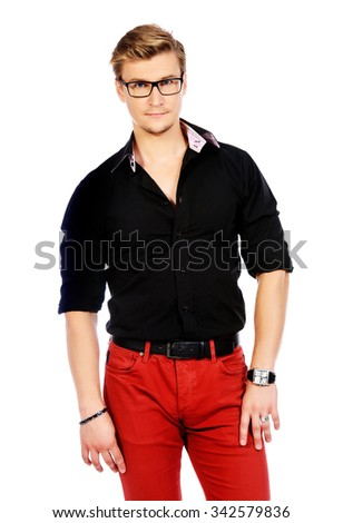 Portrait of a successful young man in spectacles looking at camera and slightly smiling.