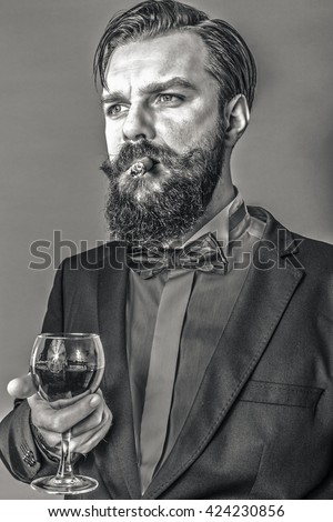 Portrait of a successful young man with retro look holding a glass of wine and smoking a cigar over gray background