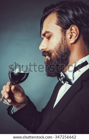 Portrait of a successful young man with retro look holding a glass of wine.Studio shot - stock photo