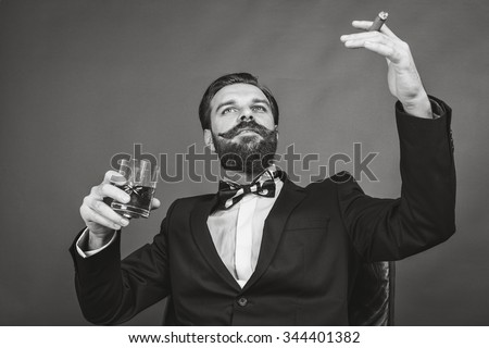 Portrait of a successful young man with retro look sitting in an armchair,smoking and holding a glass of whiskey over gray background - stock photo