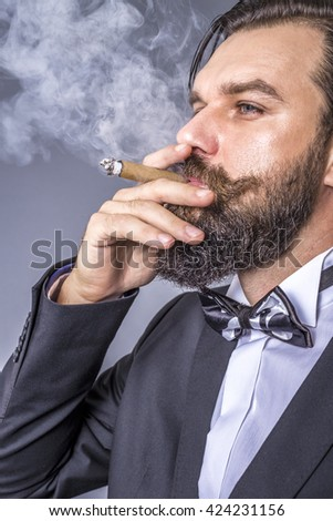 Portrait of a successful young man with retro look smoking a cigar over gray background - stock photo