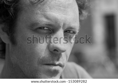 Portrait of a sultry handsome man looking towards the camera in black and white - stock photo
