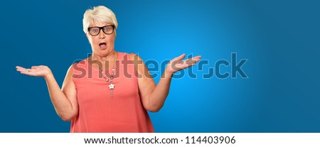 Portrait Of A Surprise Mature Woman On A Blue Background - stock photo