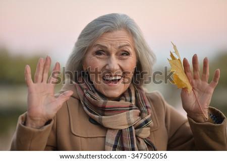 Portrait of a surprise senior woman in autumn park - stock photo