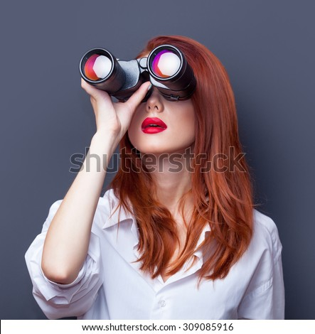 Portrait of a surprised businesswomen in white shirt with binocular on grey background. - stock photo