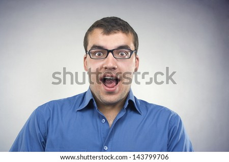 Portrait of a surprised young man in glasses and blue shirt close-up