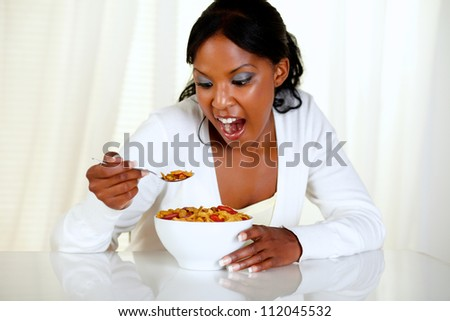 Portrait of a surprised young woman eating a bowl of cereals with strawberries at home indoor - stock photo