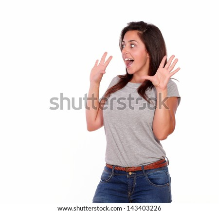 Portrait of a surprised young woman in jeans screaming with hands up while is looking to her right on isolated background - copyspace - stock photo